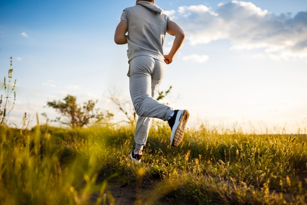 Zamyka Up Sportive Mężczyzna Jogging W Polu Przy Wschodem Słońca. Darmowe Zdjęcia