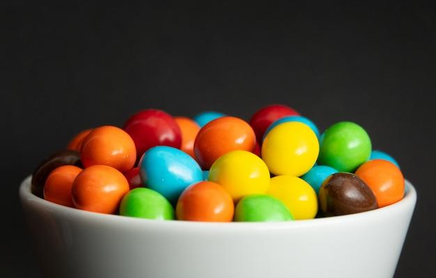 Zamyka up stos kolorowy czekoladowy pokryty cukierek, czekoladowy tło Premium Zdjęcia