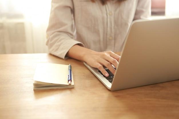 Zamyka w górę biznesowej kobiety używa laptop na drewnianym biurku Premium Zdjęcia
