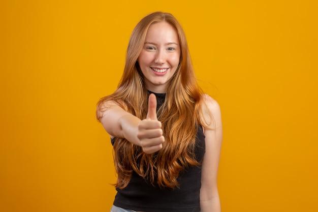 Zamyka W Górę Fotografii ładna Lisica Damy Dźwigania Kciuk W Górę Wyrażać Zgody Odzieży W Kratkę Przypadkową Koszula Koloru Odosobnioną żółtą ścianę Rudzielec Dziewczyna W Porządku. Premium Zdjęcia