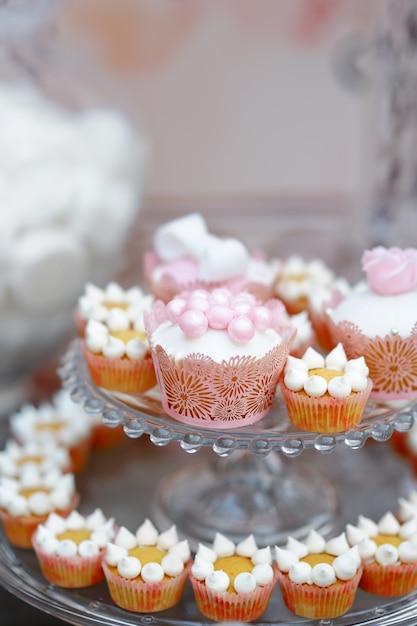 Zamyka w górę fotografii wyśmienicie złoty cukierki stół z babeczkami Premium Zdjęcia