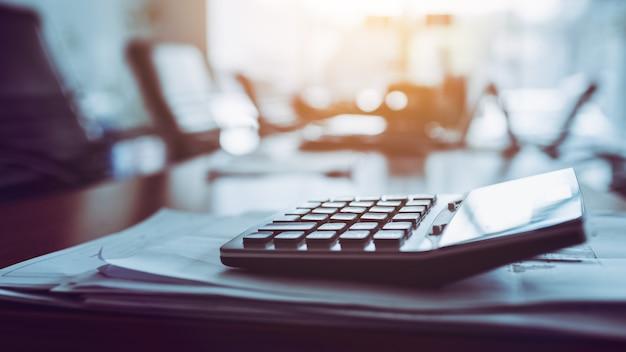Zamyka w górę kalkulatora na biznesowym pracującym biurku, ciemny tło. Premium Zdjęcia