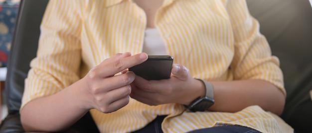 Zamyka W Górę Kobiety Trzyma Telefon Komórkowego I Używa Premium Zdjęcia