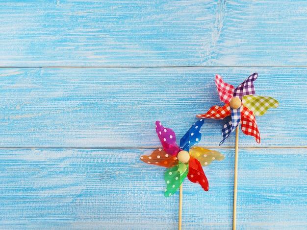 Zamyka w górę kolorowego pinwheel nad błękitnym drewnianym tłem Premium Zdjęcia