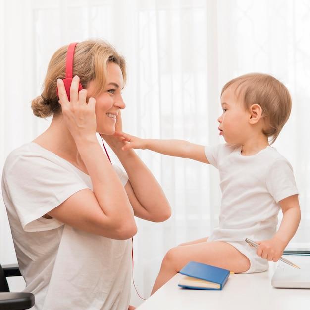 Zamyka W Górę Matki Z Hełmofonami I Dzieckiem Na Biurku Darmowe Zdjęcia
