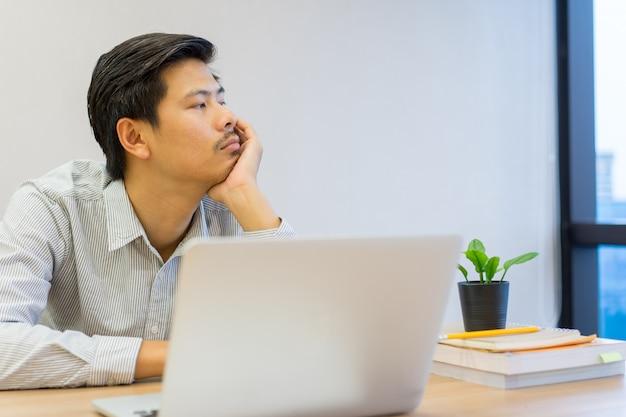 Zamyka w górę młodego azjatykciego mężczyzna uczucia znudzonego i śpiącego przy biurkiem, stylu życia pojęcie Premium Zdjęcia