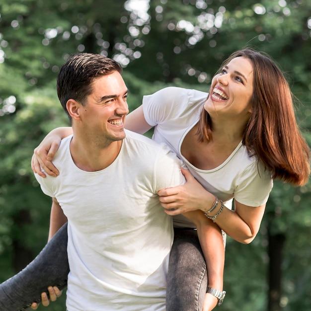 Zamyka w górę młodego człowieka niesie jego smiley dziewczyny Darmowe Zdjęcia
