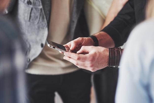 Zamyka w górę młodych przyjaciół patrzeje mądrze telefon podczas gdy siedzący w kawiarni Premium Zdjęcia