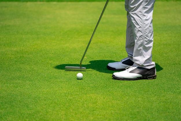 Zamyka w górę nóg golfisty i kija golfowego uderza piłkę do dziury na zielonym golfe Premium Zdjęcia