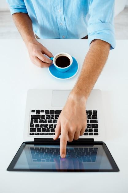 Zamyka W Górę Obrazka Młodego Biznesmena Ręki Siedzi Przy Stołem Wskazuje Na Laptopu Ekranie Trzyma Filiżankę. Białe Nowoczesne Wnętrze Biura Darmowe Zdjęcia