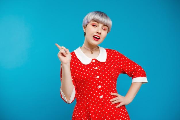 Zamyka W Górę Portret Pięknej Lalkowatej Dziewczyny Z Krótkim Jasnofioletowym Włosy Jest Ubranym Czerwieni Suknię Nad Błękit ścianą Darmowe Zdjęcia