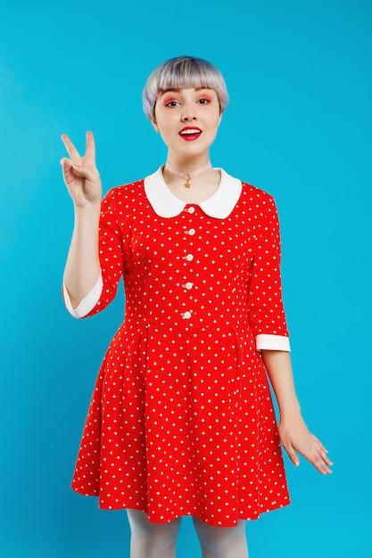 Zamyka W Górę Portret Pięknej Lalkowatej Dziewczyny Z Krótkim Jasnofioletowym Włosy Jest Ubranym Czerwieni Suknię Pokazuje Zwycięstwo Gest Nad Błękit ścianą Darmowe Zdjęcia