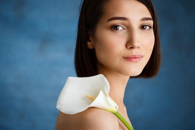 Zamyka W Górę Portreta Czuła Młoda Kobieta Z Białym Kwiatem Nad Błękit ścianą Darmowe Zdjęcia