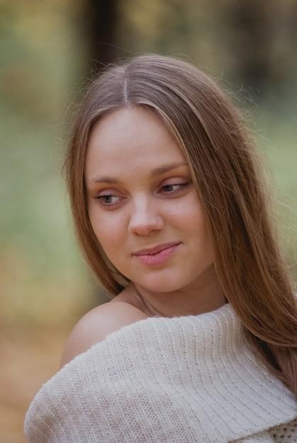 Zamyka w górę portreta piękna dziewczyna w białym pulowerze blisko kolorowych jesień liści. grafiki romantycznej kobiety. model czułości ładny uśmiechnięty Premium Zdjęcia