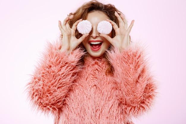 Zamyka W Górę Portreta Rozochoconej Uśmiechniętej Pięknej Brunetki Kędzierzawa Dziewczyna W Różowym Futerkowego żakieta Mienia Marshmallow Nad Biel ścianą Darmowe Zdjęcia