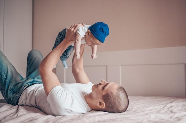 Zamyka W Górę Portreta Szczęśliwy Młody Tata Ojciec Trzyma Jego Dziecka W Niebieskich Dżinsach, Białej Koszulce I Nakrętce. Młoda Szczęśliwa Rodzina, Tata Bawi Się ślicznym Emocjonalnym Małym Synkiem Nowonarodzonego Dziecka W Sypialni. Premium Zdjęcia
