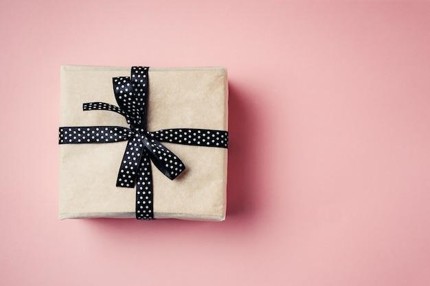 Zamyka w górę prezenta pudełka z czarnym faborkiem na różowym tle, odgórny widok Premium Zdjęcia
