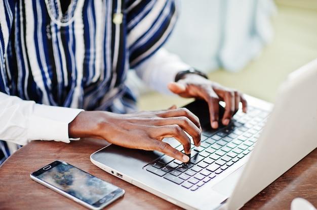Zamyka W Górę Ręk Afrykański Mężczyzna Siedzi Za Laptopem I Działaniem W Tradycyjnych Ubraniach Premium Zdjęcia