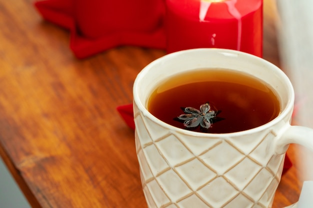 Zamyka W Górę Strzału Filiżanki Herbata Na Drewnianej Desce Przy Bożenarodzeniowym Wnętrzem Premium Zdjęcia