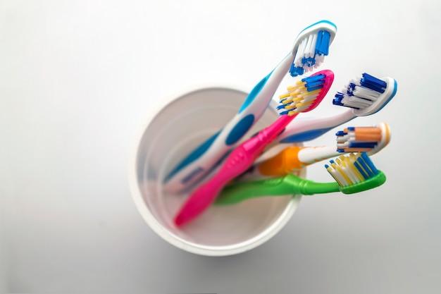 Zamyka W Górę Strzału Set Stubarwni Toothbrushes W Szkle Na Czystej Toalecie, Pojęcie Stomatologiczny. Premium Zdjęcia
