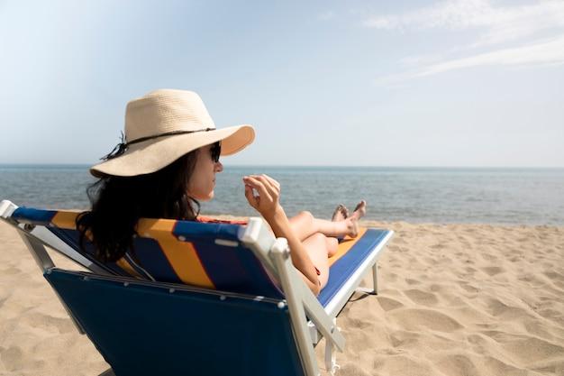 Zamyka W Górę Tylnego Widoku Kobiety Na Plażowym Krześle Patrzeje Daleko Od Darmowe Zdjęcia