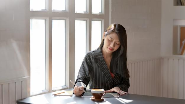 Zamyka W Górę Widoku Kobieta Używa Cyfrową Pastylkę Z Stylus W Ciemnym Nowożytnym Miejscu Pracy Premium Zdjęcia