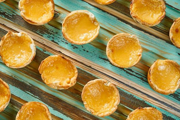 Zamyka W Górę Widoku Na Smakowitym Pastelowym De Nata - Portugalski Tarta Jajeczny Tarta Ciasto Odkurzający Z Cynamonem Na Drewnianym Stole. Piekarnia. Premium Zdjęcia