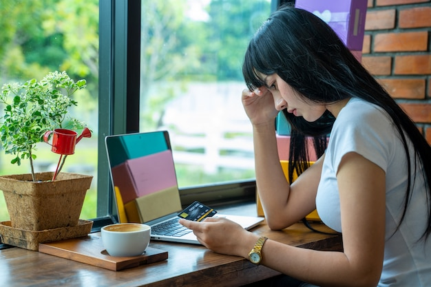 Zamyka W Górę Wizerunku Azjatycka Kobieta Stresuje Się Z Kartą Kredytową, Azjatycka Kobieta Próbuje Znajdować Pieniądze Spłacać Dług Karty Kredytowej. Premium Zdjęcia