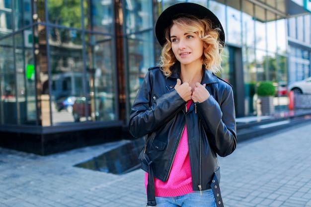 Zamyślona Blond Krótkowłosa Kobieta Spacerująca Po Ulicach Dużego Nowoczesnego Miasta. Modny Strój Miejski. Niezwykłe Różowe Okulary Przeciwsłoneczne. Darmowe Zdjęcia