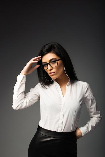 Zamyślona brunetka w okularach, w białej bluzce z czarną skórzaną spódnicą. Premium Zdjęcia