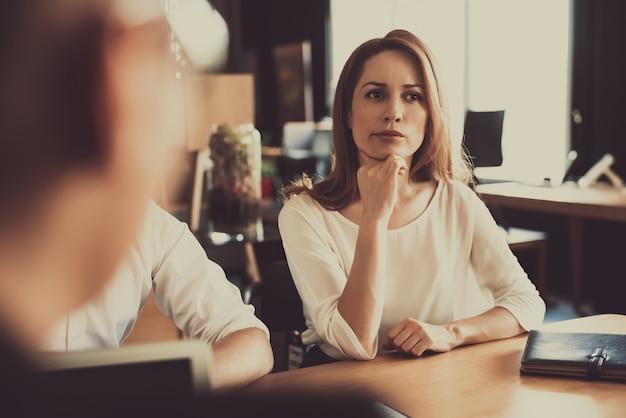 Zamyślona czerwona z włosami kobieta siedzi na rozmowie Premium Zdjęcia