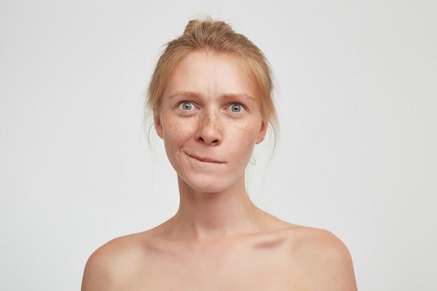 Zamyślona Młoda Atrakcyjna Ruda Kobieta Z Fryzurą Kok, Gryząca Dolną Wargę I Patrząc Zdezorientowana W Kamerę, Pozująca Na Białym Tle Z Nagimi Ramionami Darmowe Zdjęcia
