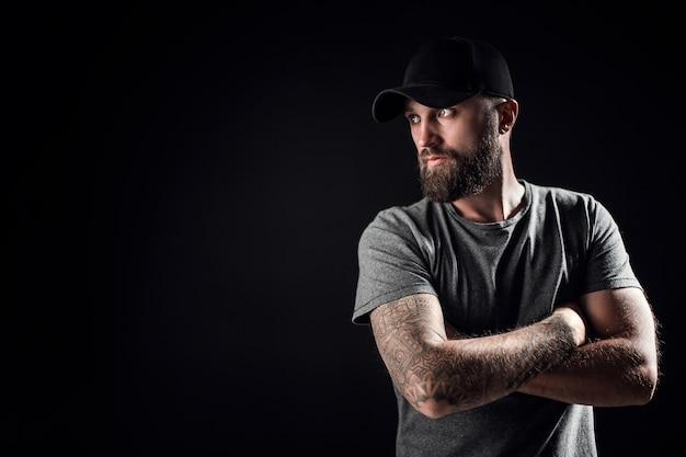 Zamyślony Czarny Brodaty Mężczyzna Ubrany W Szarą Koszulę, Okulary Przeciwsłoneczne I Czapkę Baseballową. Premium Zdjęcia