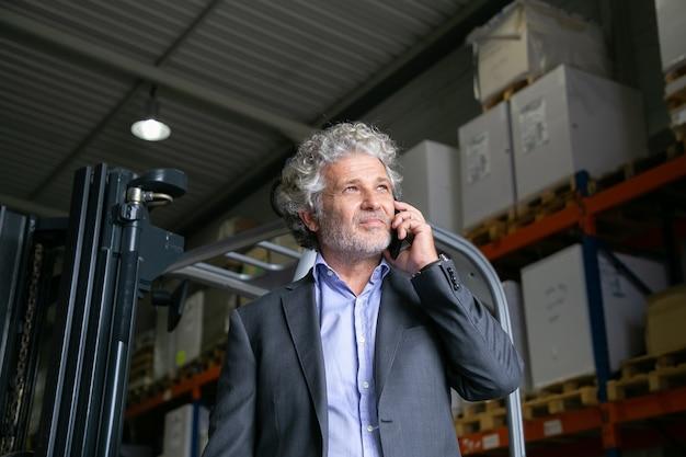 Zamyślony Dojrzały Biznesmen Stojący W Pobliżu Wózka Widłowego W Magazynie I Mówiąc Na Telefon Komórkowy. Półki Z Towarami W Tle. Koncepcja Biznesowa Lub Logistyczna Darmowe Zdjęcia