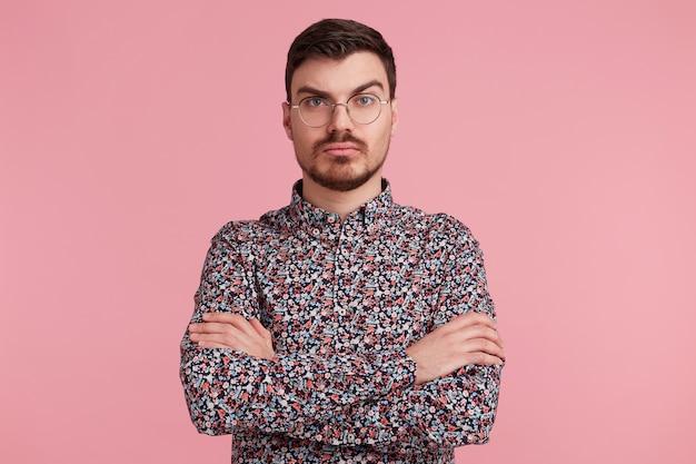 Zamyślony Młody Brodaty Mężczyzna W Okularach W Kolorowej Koszuli, Myśląc O Czymś, Stojąc Z Rękami Skrzyżowanymi Z Jedną Uniesioną Brwią Pytający, Z Poważnym I Zdziwionym Wyrazem Twarzy Na Różowej ścianie Darmowe Zdjęcia