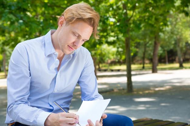 Zamyślony student koncentruje się na notatkach Darmowe Zdjęcia