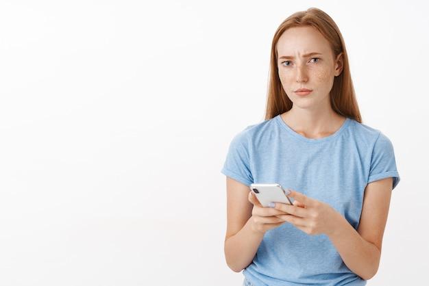 Zaniepokojona Kobieta Nie Może Zrozumieć Sensu Przekazu, Wygląda Na Zakwestionowaną I Skupioną Zmarszczoną Brwi, Mrużąc Oczy Podczas Myślenia O Ponownym Rozważeniu Oferty, Trzymając Smartfon Darmowe Zdjęcia