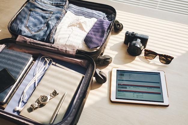 Zapakowana walizka na biurku, tablecie z eticket na ekranie, aparacie i okularach przeciwsłonecznych Darmowe Zdjęcia