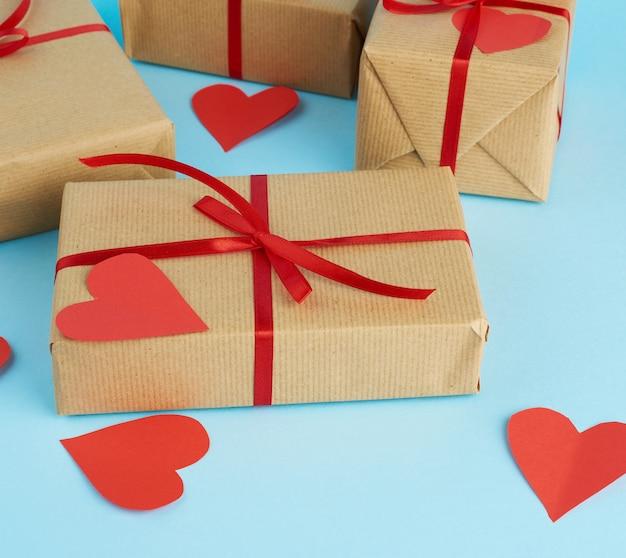 Zapakowane Prezenty W Brązowy Papier Pakowy I Przewiązane Czerwoną Wstążką Na Niebieskim Premium Zdjęcia