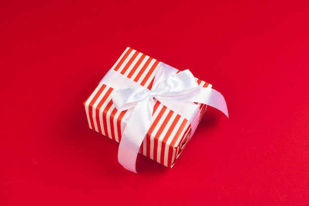 Zapakowane pudełko na czerwonym tle, widok z góry Premium Zdjęcia