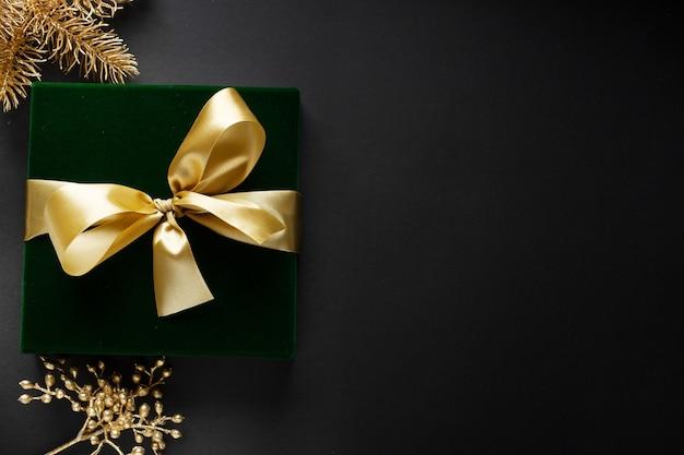 Zapakowany Złoty Prezent Ze Złotą Kokardką I Bombkami Na Ciemnym Tle. Premium Zdjęcia