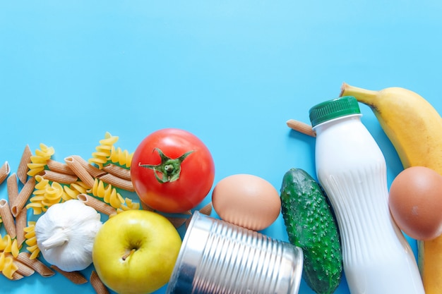Zapasy żywności, Zapas żywności Kryzys Na Okres Izolacji Kwarantanny Na Niebieskim Tle. Makaron, Pomidor, Konserwy, Ogórek, Jabłko, Banan, Czosnek. Premium Zdjęcia