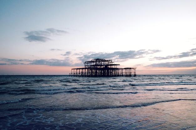 Zapierający Dech W Piersiach Widok Na Spokojne Morze Pod Zachmurzonym Niebem O Zachodzie Słońca Darmowe Zdjęcia