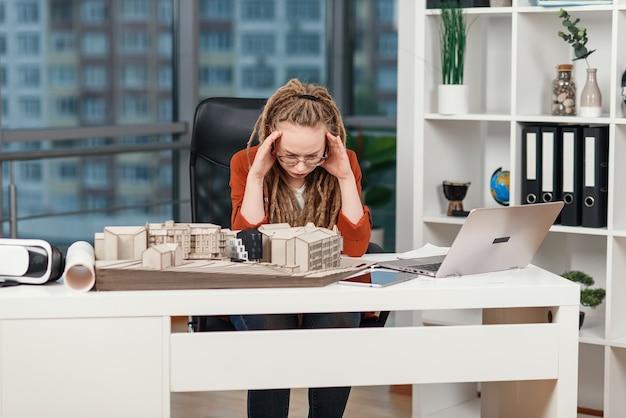 Zapracowana Kobieta Biznesu Odczuwa Stres Związany Z Problemami Z Projektem Architektonicznym I Projektowym Przyszłego Budynku. Premium Zdjęcia