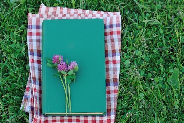 Zarezerwuj z pustą okładką na trawie, widok z góry. czytanie na świeżym powietrzu, letnie wakacje. Premium Zdjęcia