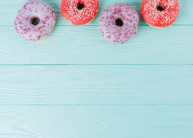 Zasięrzutnego widoku świezi donuts układali z rzędu na drewnianym stole Darmowe Zdjęcia