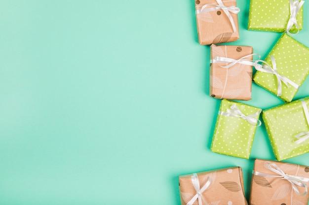 Zasięrzutny widok brown i zielony papier zawijający prezentów pudełka na zielonym tle Darmowe Zdjęcia