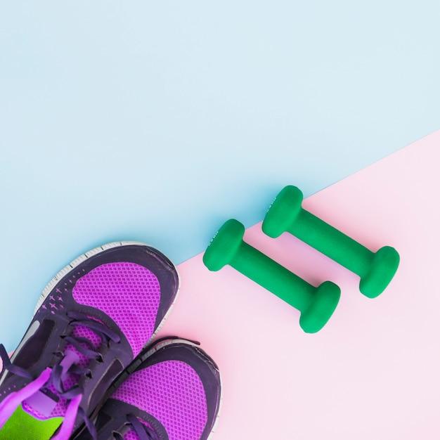 Zasięrzutny widok dwa zielonego dumbbells i para buty na podwójnym tle Darmowe Zdjęcia