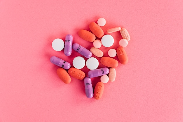 Zasięrzutny widok kolorowe pigułki na różowym tle Darmowe Zdjęcia