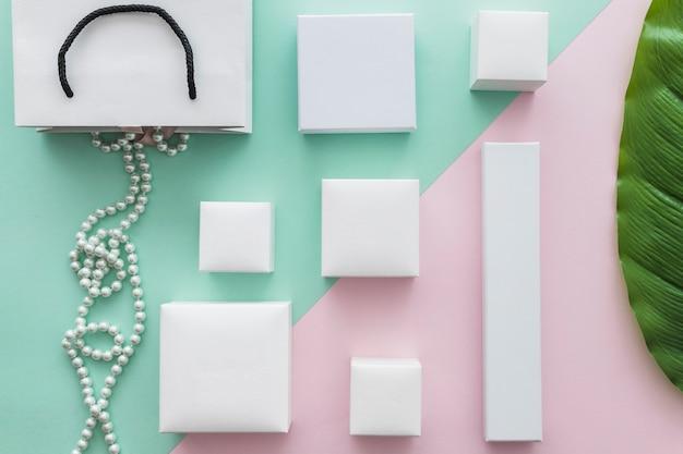 Zasięrzutny Widok Perła Kolia Z Wiele Białymi Pudełkami Na Papierowym Tle Darmowe Zdjęcia